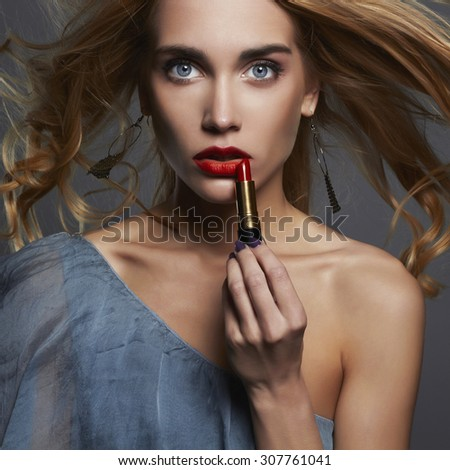 beautiful girl with red lipstick. young Woman putting lipstick. healthy hair