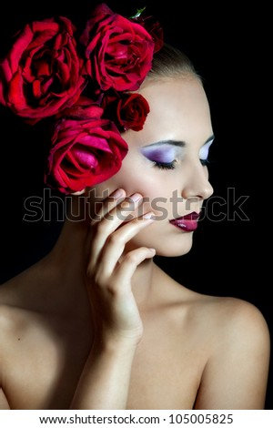 Beautiful girl with red roses in her hair