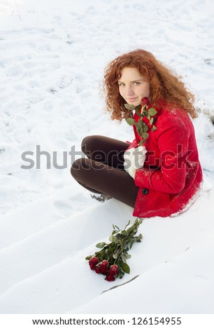 Beautiful girl with roses in the snow in winter - stock photo