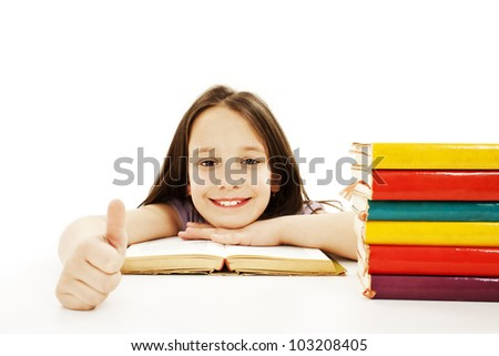 Beautiful girl with school books on the table, showing OK sign. Isolated on white background - stock photo