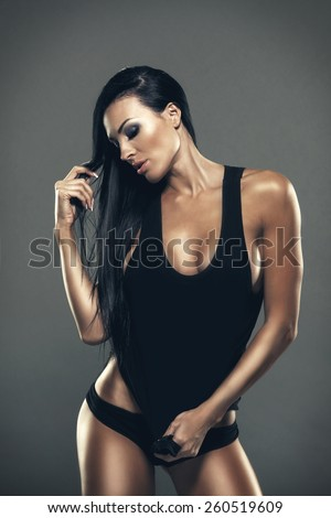 Beautiful girl with sexy breasts in black t-shirt with long black hair - stock photo