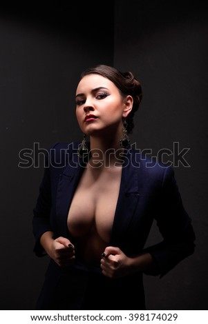 Beautiful girl with sexy breasts in jacket and beauty hair studio