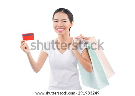 Beautiful girl with shopping bags and credit card. Happy asian woman shopping with a credit card - isolated over white - stock photo