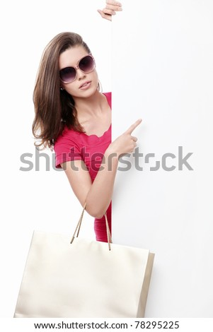 Beautiful girl with shopping bags and empty the board on a white background - stock photo