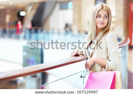 Beautiful girl with shopping bags in store