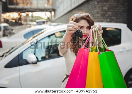 beautiful girl with shopping bags near a her car, shows in the picture with shopping bags and car keys - stock photo