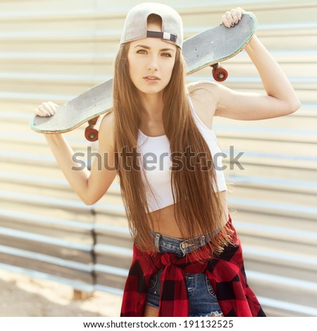 Beautiful girl with skateboard in the hands against the wall