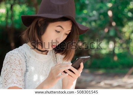 Beautiful? girl  with smartphone in park
