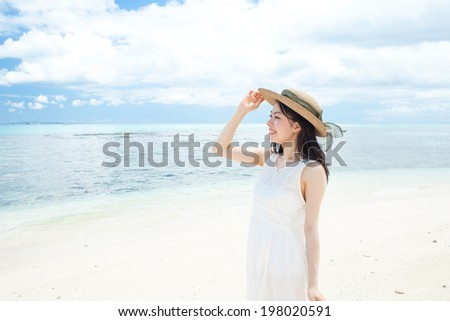 beautiful girl with straw hat on the tropical island beach