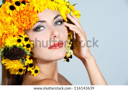 beautiful girl with stylish makeup and yellow and orange flowers around her head - stock photo