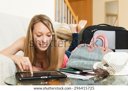 Beautiful girl with  suitcase searching for travel destination on digital tablet in home interior