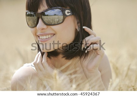 beautiful girl with sunglasses in the wheat field - stock photo