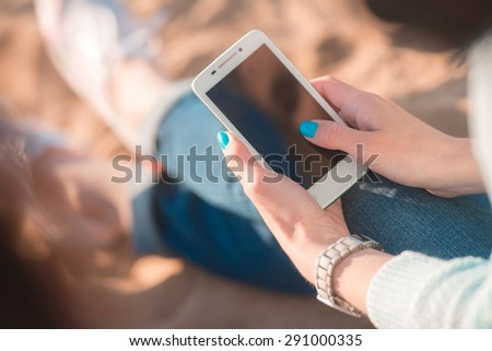 Beautiful girl with the phone in hands on the beach