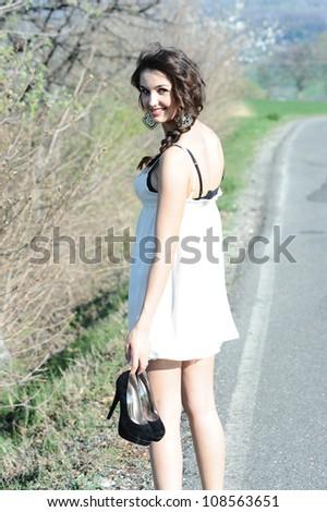 beautiful girl with the white dress walking barefoot near a field - stock photo