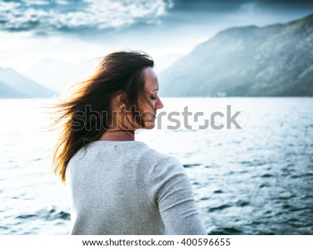 Beautiful girl with tousled hair on the background of the Bay in Montenegro