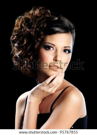 Beautiful  girl with trendy hairstyle and bright eye make-up - on black background - stock photo
