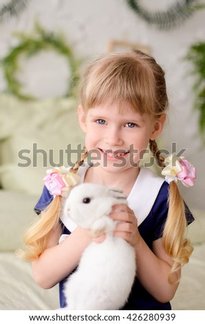 beautiful girl with two braids, smiling, holding a white rabbit