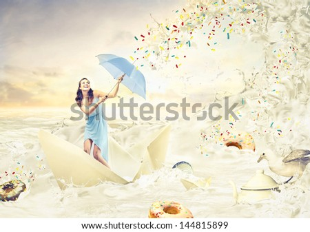beautiful girl with umbrella on a boat sailing in a sea of ??sweet - stock photo