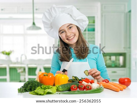 beautiful girl with vegetables cooking on a kitchen