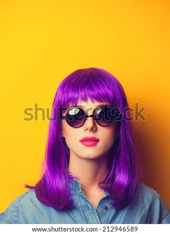 Beautiful girl with violet hair in sunglasses on yellow background. - stock photo
