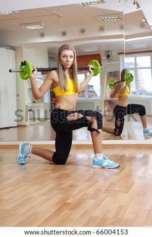 Beautiful girl with weight gym indoors - stock photo