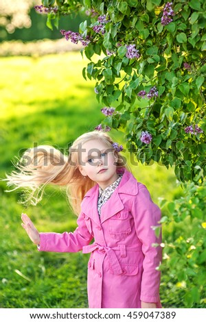 beautiful girl with white hair and blue eyes in a pink raincoat will lilac bush