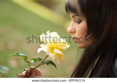 Beautiful girl with yellow rose, soft background - stock photo