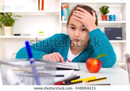 Beautiful girl working on her school project at home. - stock photo