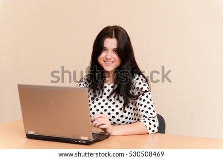 Beautiful girl works for laptop