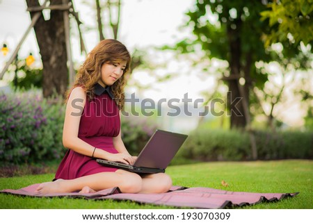 Beautiful girl works with laptop in the garden