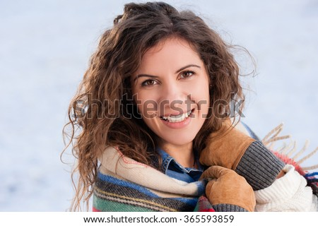 Beautiful girl wrapped in blanket in snow, looking and smiling at camera.