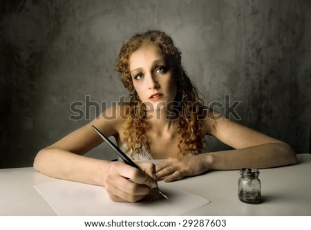 Beautiful girl writing a letter with ink pen - stock photo