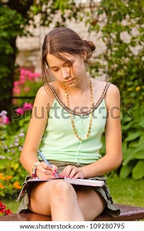 Beautiful girl writing into her diary - stock photo