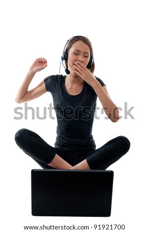 beautiful girl yawning in the headphones with a laptop on his knees on a white background