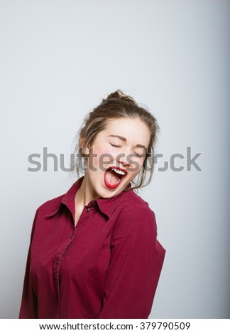 Beautiful girl yawning, isolated on a gray background