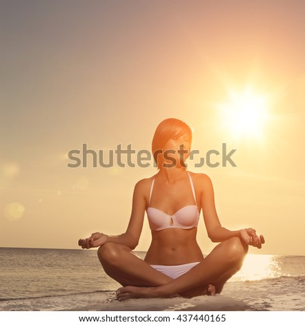 Beautiful girl yoga on the beach at sunset.  Woman resting in the sun - stock photo