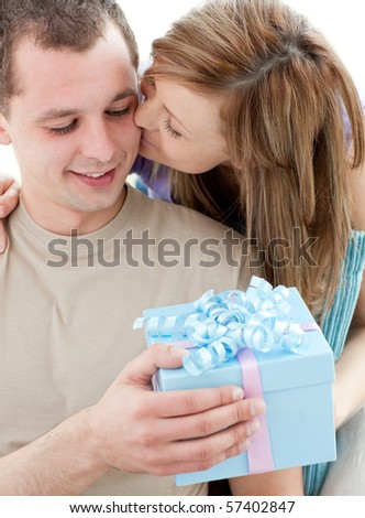 Beautiful girlfriend giving a present and a kiss to his handsomel boyfriend against white background - stock photo