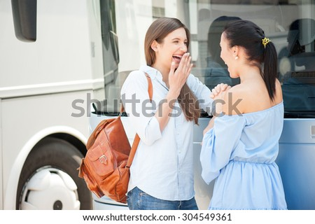 Beautiful girls are gossiping near a bus. They are waiting for bus departure. The friend are laughing and looking at each other happily - stock photo