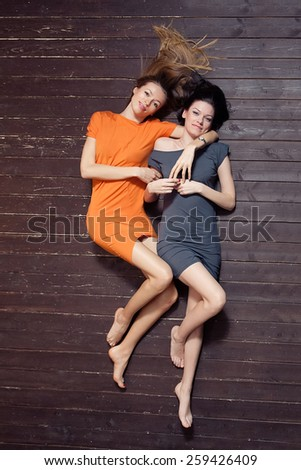 Beautiful girls are laying on the wooden floor.  - stock photo