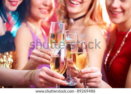 Beautiful girls clink glasses of champagne at a party - stock photo