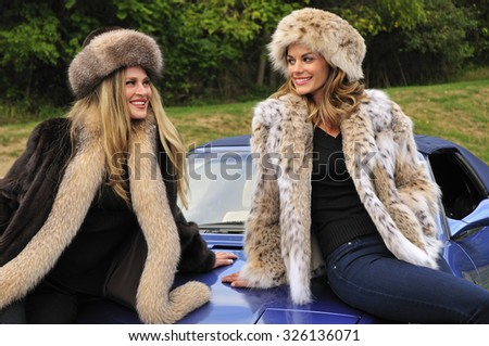 beautiful girls dressed in winter fashion sitting on a hood of a sports car - stock photo