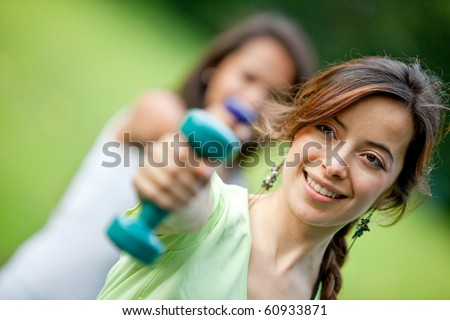 Beautiful girls exercising outdoors with free weights - stock photo