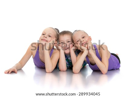 Beautiful girls gymnasts next to his younger brother - isolated on white background - stock photo