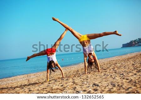 Beautiful girls having fun at beach - stock photo