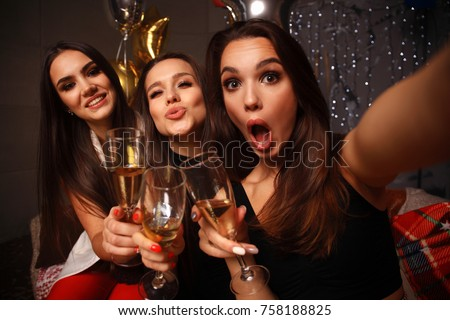 Beautiful girls having party fun, drinking champagne. Holidays, celebration, nightlife and people concept - smiling friends dancing in club
