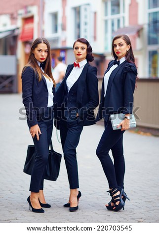 beautiful girls in black suits posing on the street - stock photo