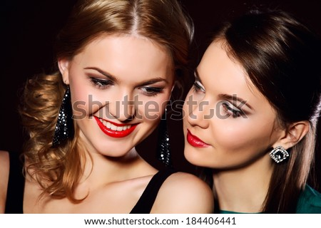 Beautiful girls in colorful dresses fashion studio dark background - stock photo