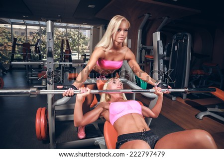 Beautiful girls in fitness club out exercise with a bar in the gym Bar Bench Press  - stock photo
