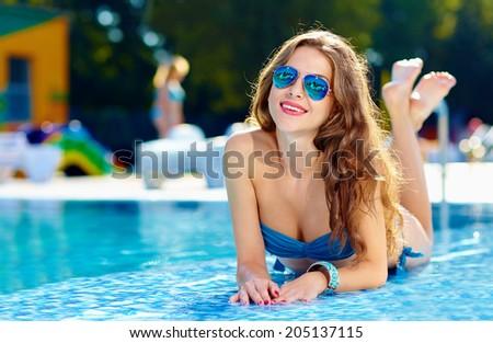 beautiful girls lying near swimming pool - stock photo