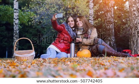 Beautiful girls making selfie on a picnic in autumn park sitting  the fallen leaves near the pumpkin at halloween time.
